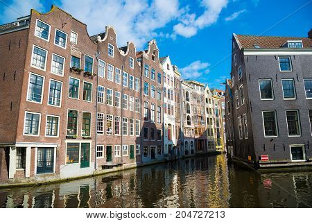 Classical View Of Traditional Buildings At The Canal Side In Amsterdam Downtown.