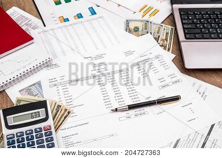 Financial Concept With Laptop, Dollar And Business Report, Fountain Pen And Calculator At Office