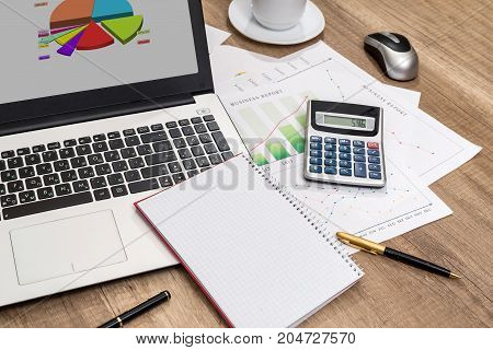 Business Workplace With Laptop, Graph, Pen And Calculator