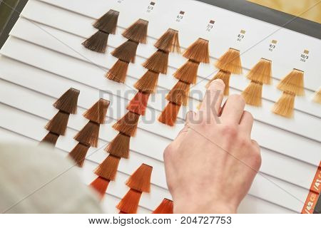 Hair dye sample chart, hand. Different colors of hair.