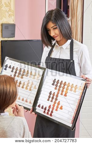 Stylist holding hair swatches chart. Woman choosing hair dye color. Free hairdresser consultation.