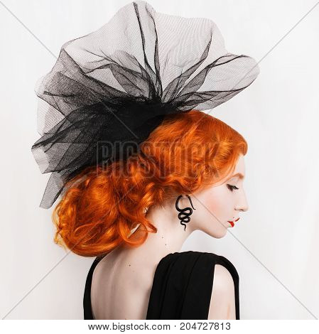 Veil on head. Redhead woman in veil with unusual appearance in black dress and veil on the head and red lips. Girl in veil with pale skin and a beautiful antique necklace on neck and black earrings in the form of snakes.
