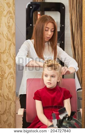 Hairdresser working with little girl. Kid in hair salon.