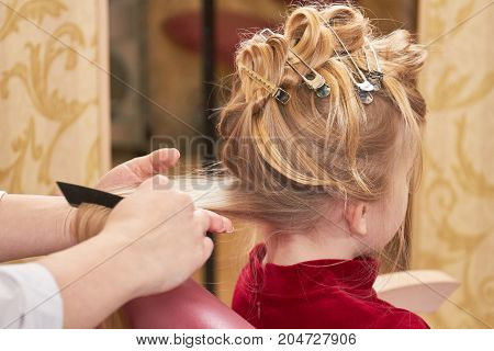 Little girl getting hair done. Hands of hairstylist working.