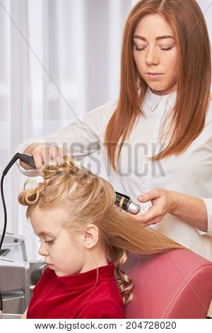 Kid getting hair done. Female hairdresser using curling iron.