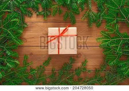 Christmas background. Present box in craft paper bounded with red satin ribbon. Gift framed with green pine tree branches on wooden table. Handmade leisure and winter holidays concept