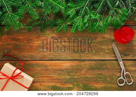 Christmas DIY background. Present box, scissors and string jute on rustic wood with fir tree branches border. Handmade hobby and winter holidays concept, top view, copy space.