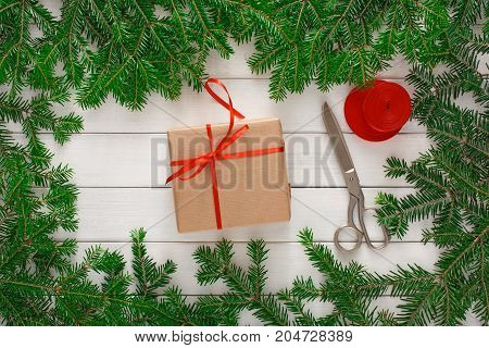 Christmas DIY background. Present box, scissors and string jute on white rustic wood with fir tree branches border. Handmade hobby and winter holidays concept, top view, copy space.