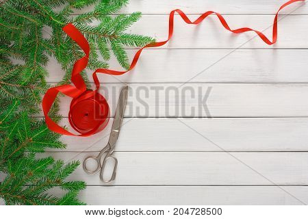 Christmas DIY background. Scissors and red satin ribbon on white wood with fir tree branches border. Handmade hobby and winter holidays concept, top view, copy space.