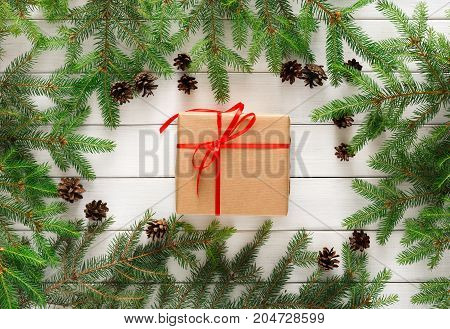 Christmas background. Present box in craft paper bounded with red satin ribbon. Gift framed with green pine tree branches on white wooden table. Handmade leisure and winter holidays concept