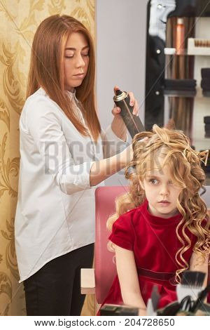 Stylist using hairspray, little girl. Child in hairdressing salon.