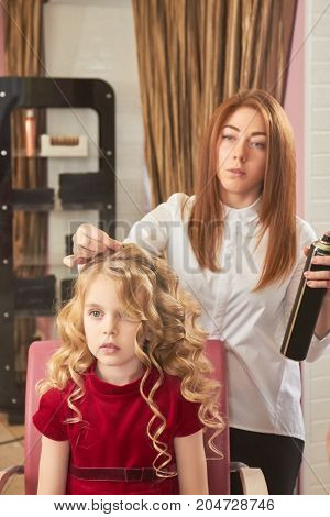 Little girl and female hairstylist. Woman holding hairspray bottle.
