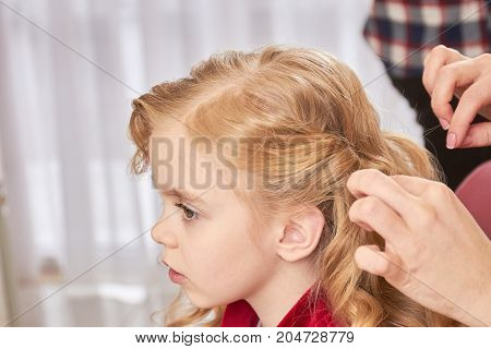 Little girl, hands of hairstylist. Face of kid, side view.