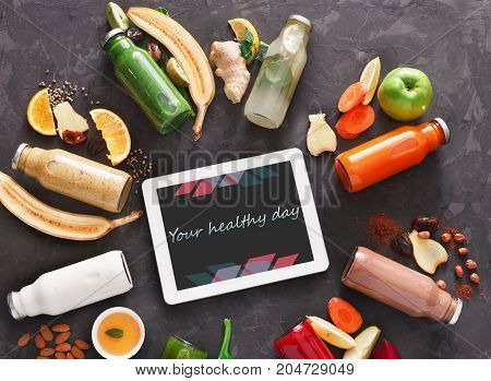 Healthy detox drinks with fruit and vegetable ingredients and tablet with copy space on screen at black background. Glass bottles with smoothie, top view, flat lay. Internet order online concept
