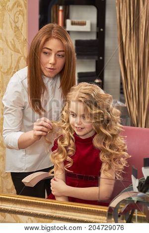 Smiling little girl and hairdresser. Cute kid in hair salon.