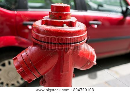 Red fire hydrant water pipe near the road. Fire hydrant for emergency fire access.