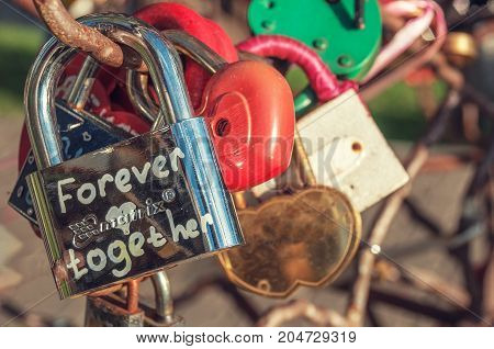 Metallic shiny lock with the inscription forever together hanging among other heart-shaped locks