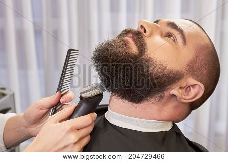 Beard trimming in barbershop. Hands of barber, trimmer and comb.