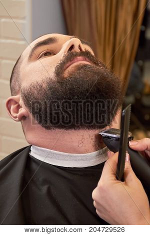 Beard trimming in barber shop. Hands of female barber working.