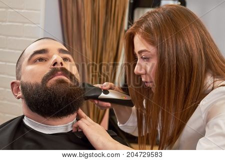 Barber working with bearded customer. Young man in barbershop.