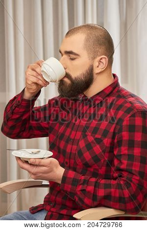 Bearded man drinking coffee. Caucasian male holding white cup. The taste of manliness.