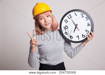 Asian Engineer Woman Show Victory Sign With A Clock.