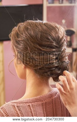 Hand of stylist, braided hairdo. Woman with brown hair.