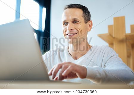 Successful results. Cheerful positive ambitious businessman looking at the laptop screen and smiling while seeing successful results