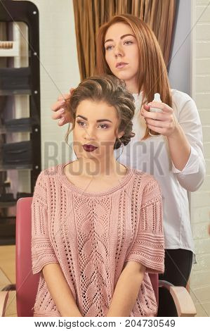 Woman in a hairdressing salon. Stylist holding hair lotion bottle. Professional hair setting lotion.