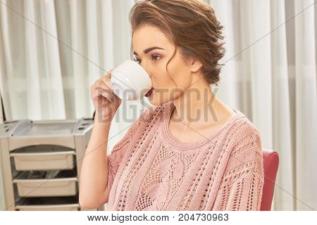 Woman in hair salon, coffee. Girl drinking from a cup. Beauty benefits of coffee.