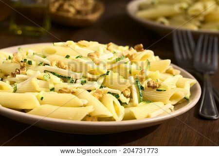 Penne pasta with zucchini and ham stripes and walnut photographed with natural light (Selective Focus Focus one third into the dish)