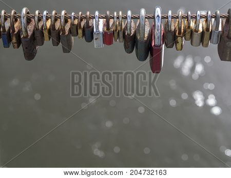 Colorful Locks Hanging From High Wire Of Bridge With Bokeh Lights On Gray Water Background