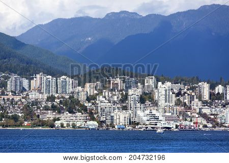 Modern buildin skyline of West Vancouver district surrounded by mountains (Vancouver British Columbia).