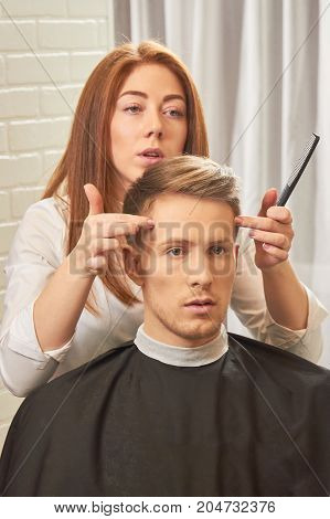 Female barber busy with client. Hairdresser holding a comb.
