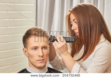 Man getting a haircut. Barber woman using hair clipper.