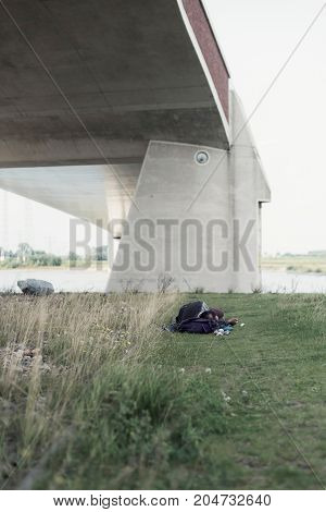 Rambler Sleeps In Grass Under Modern Bridge Near River.