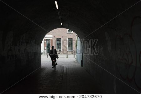Silhouette Of Woman Cycling In Urban Tunnel.