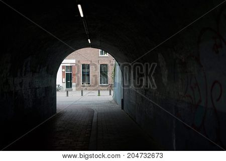 Dark Bike Tunnel With Houses At The End.