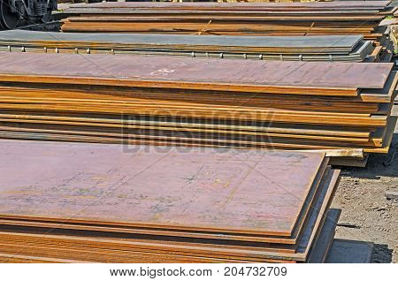 The rusty hot-rolled sheet metal in packs at the warehouse of metal products piled in the open air