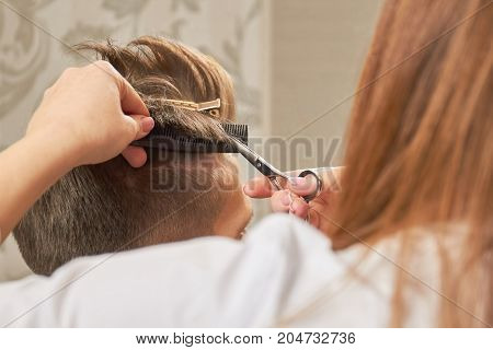 Hands with scissors cutting hair. Barber shop customer getting haircut.
