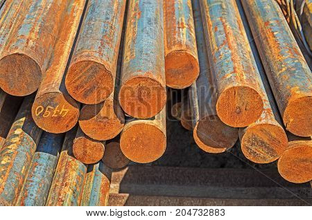 The rusty hot-rolled round steel bars in packs at the warehouse of metal products piled in the open air