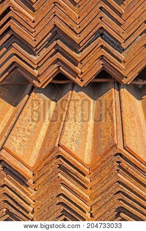 The rusty metal L-bar angle in packs at the warehouse of metal products piled in the open air