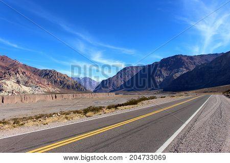 Estrada deserta que conduz a montanhas desconhecidas e misteriosas