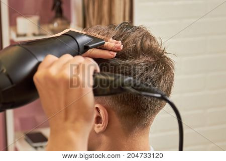 Barber drying hair close up. Work of hairstylist with client. Hair dryers recommended by stylists.