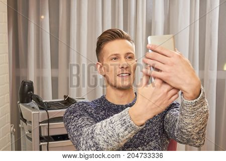 Man in barbershop holding phone. Handsome guy indoor. Video calling apps.