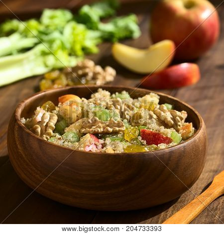 Quinoa Waldorf Salad with apple celery yellow raisins and walnut served in wooden bowl ingredients in the back photographed on dark wood with natural light (Selective Focus Focus one third into the salad)