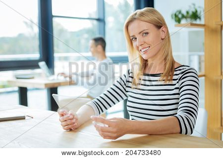 Futuristic technology. Pleasant nice attractive woman having a tablet in her hands and smiling while sitting at the table in the office