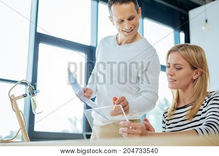 Help me please. Pleasant nice attractive woman holding a tablet and showing its screen to her colleague while asking his advice