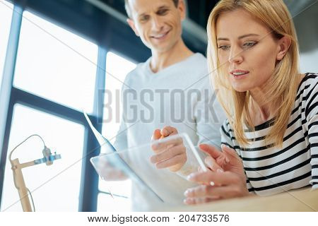 Professional cooperation. Pleasant smart friendly man standing behind his colleague and holding a pencil while pointing at the tablet screen