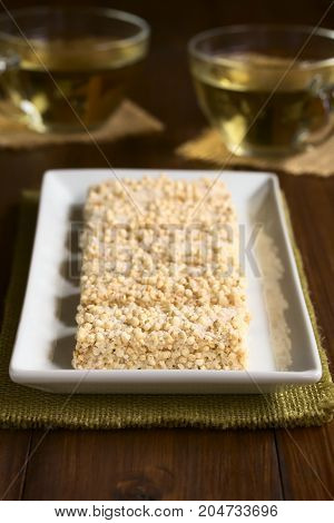 Baked marshmallow popped quinoa and coconut bars on white plate photographed with natural light (Selective Focus Focus on the front of the first bar)